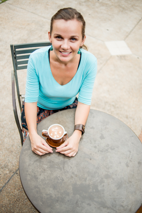 A girl in a teal jumper drinking coffee outdoors - tips for better portrait photo shoot