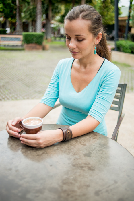 A girl in a teal jumper drinking coffee outdoors