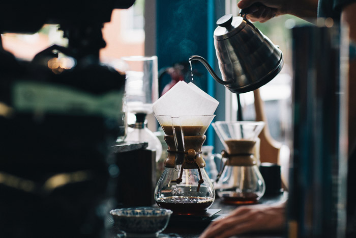 A barista pouring coffee into a v60 filter at a busy cafe - how to write a successful photography business plan