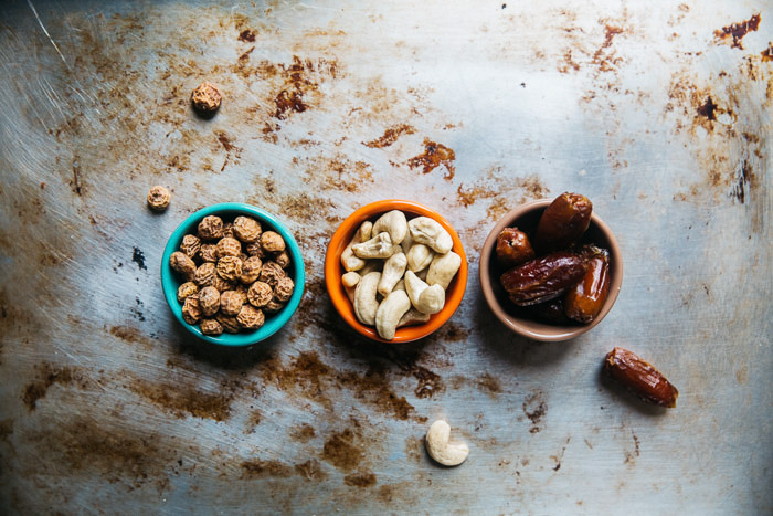 An overhead shot of three small bowls of nuts and dried fruit on a metal surface