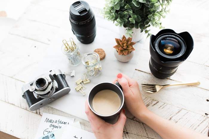 Overhead shot of a person holding a coffee cup at a table with plants, camera, lenses and other photography equipment