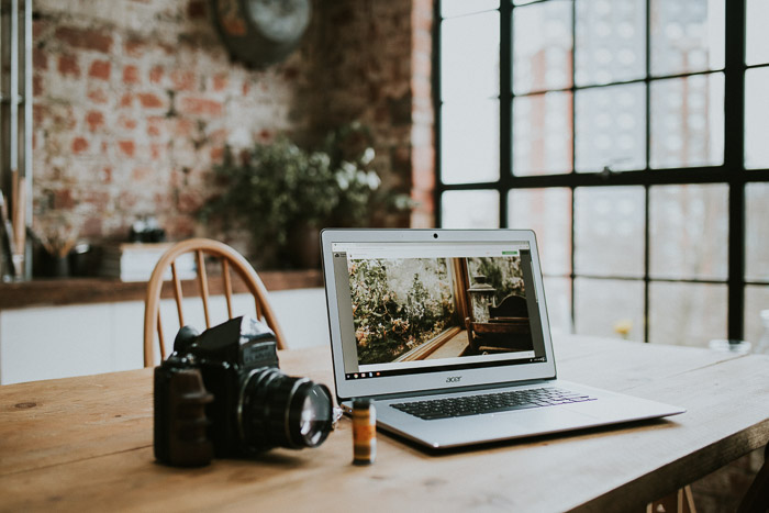 A laptop, film and camera set up on a wooden desk to prepare a photography business plan