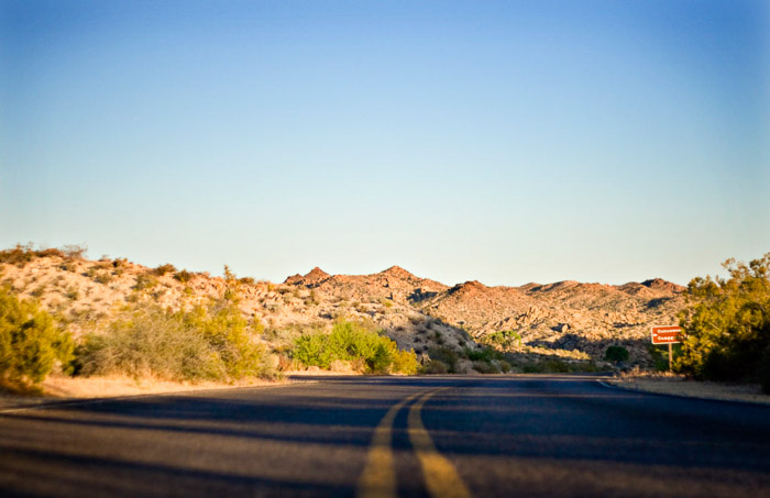 A low angle photo of a highway in a rocky landscape setting - photography business tips