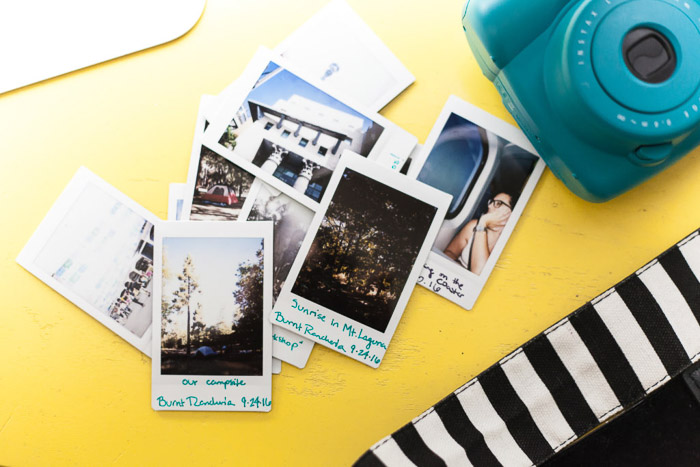 A pile of photos from an instant camera on a yellow surface - how to start a photography business
