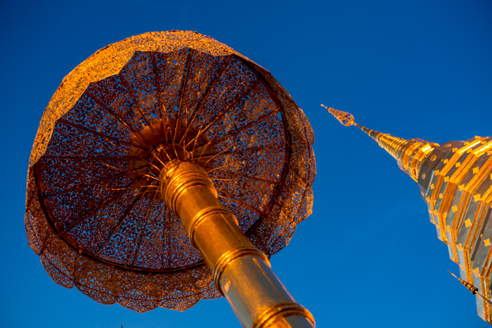 photo looking up at the Golden stupa and umbrella in buddhist temple in Chiang Mai, Thailand against a deep blue sky