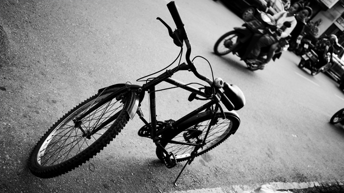 an angled black and white photo of a bicycle parked by the street
