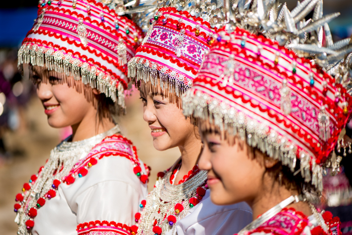 three smiling girls wearing red and white traditional headdresses and costumes