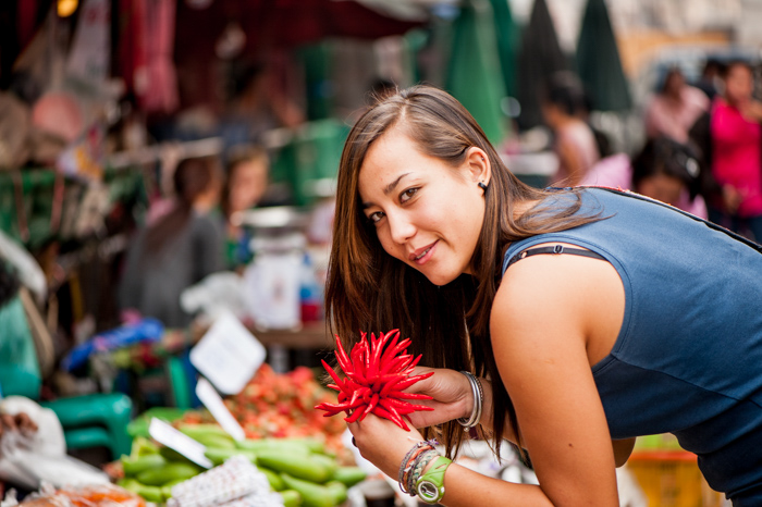 A brunette woman in a sleeveless navy shirt smiling and leaning over wares in a fresh marketplace