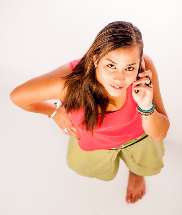 A photography composition example of a brunette woman in a red shirt speaking on her cellphone looking up