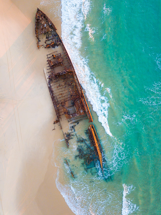aerial view of a shipwreck on a tropical shore