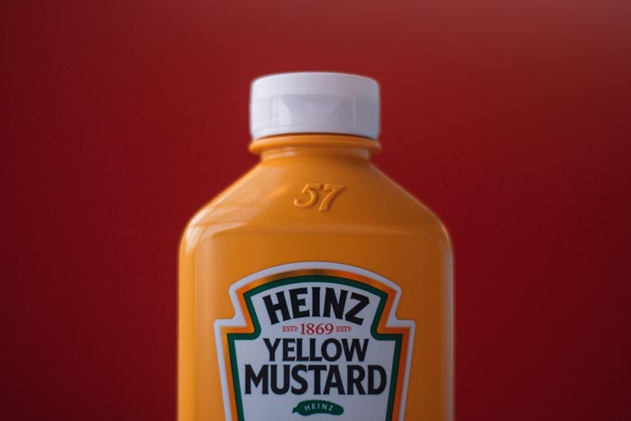 A close up shot of a bottle of Heinz mustard against a red background - interesting product photography composition