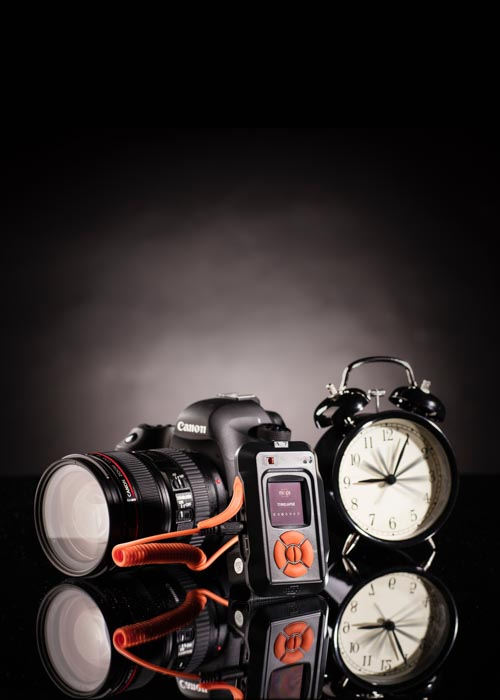 A product photography still life of a DSLR camera and alarm clock against a black background