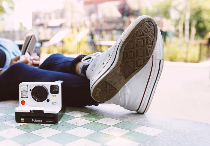 A polaroid camera on a stone table beside a persons crossed legs - product photography composition rules