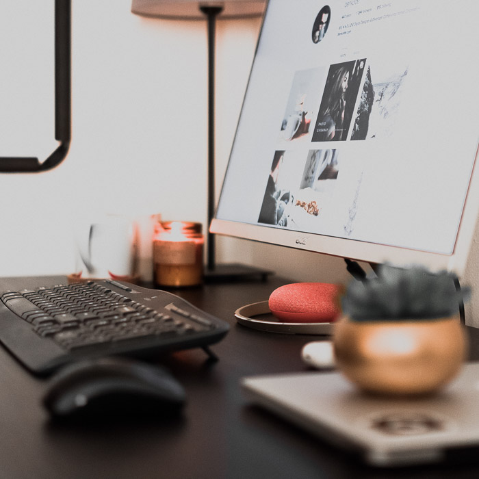 An office desk containing a computer, plant, lamp and other accessories - real state photography marketing