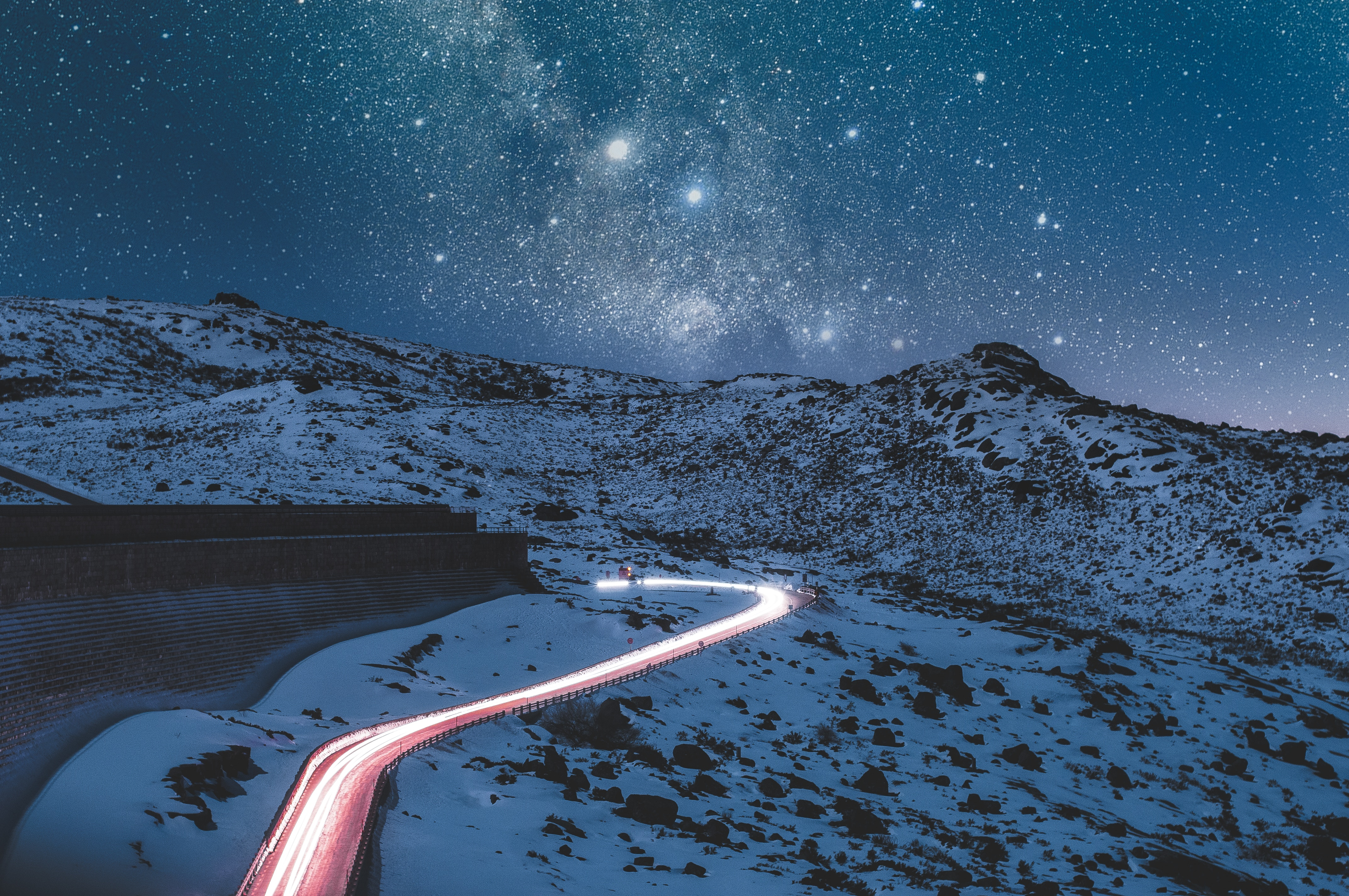 Photo of a light trail of a road going into the snowy mountains at night with a starry sky above