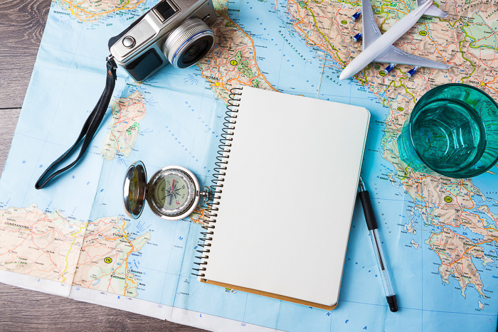 An overhead shot of a camera, notebook,pen and model plane on top of a map of the world