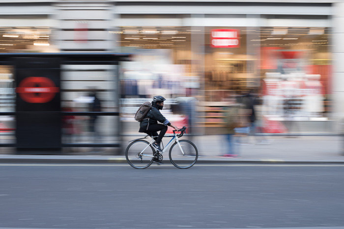 A person riding a bicycle in the city, the background is a creative blur due to using slow shutter speed