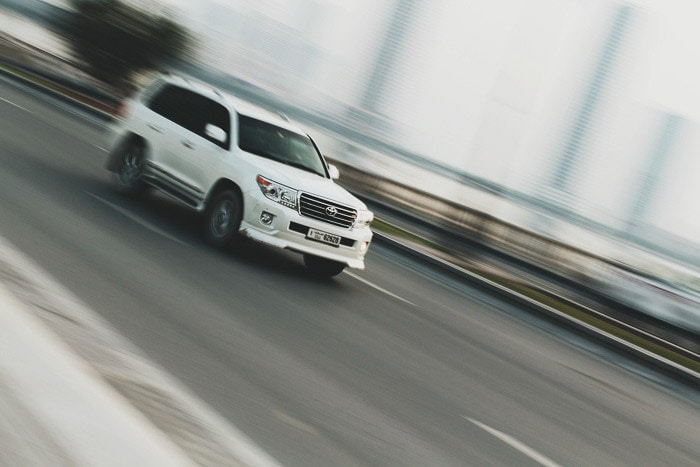 A white car driving, the background is a creative blur demonstrating shutter speed and its uses
