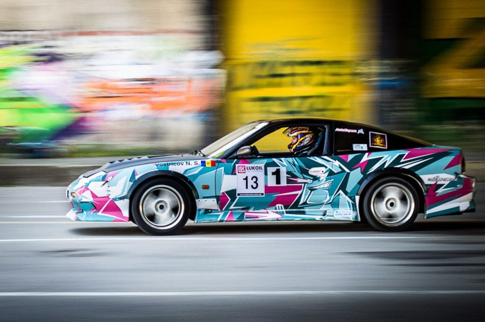 A colourful race car driving with motion blur background