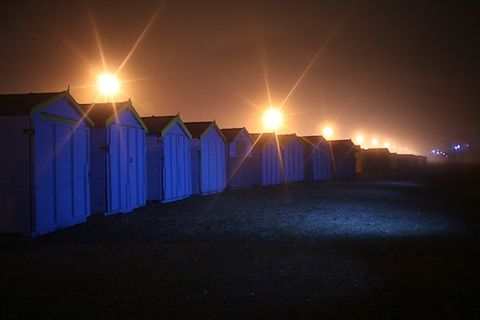A night photography shot of a line of small wooden cabins