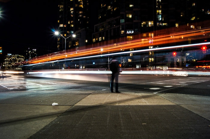 A man standing on a street at night, a stream of light trails in front of him