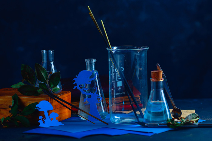 A still life featuring glass bottles ,silhouettes of tiny cut out character, incense