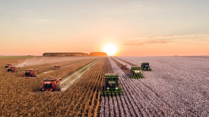 An image of farm machinery working in a field at sunset - what are stock photographs