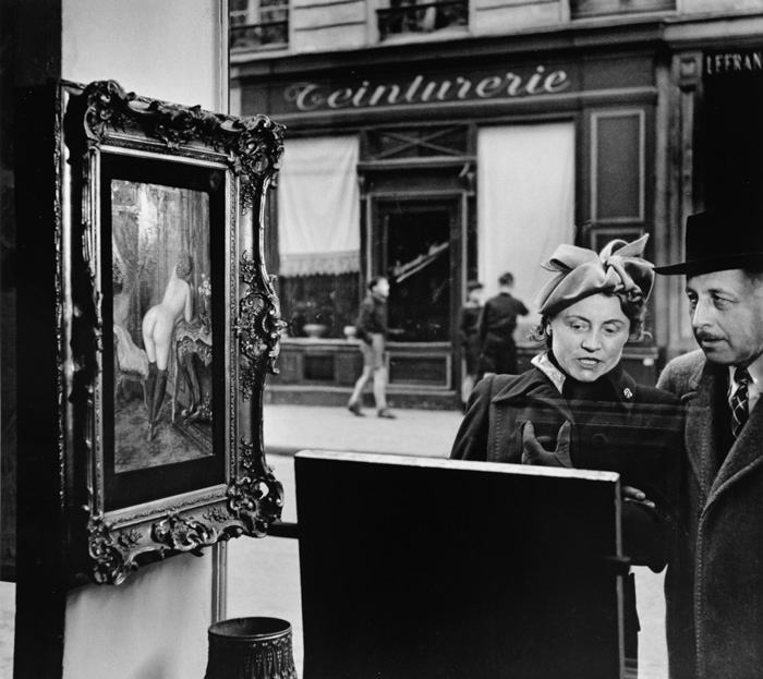 A candid shot of a couple looking at paintings in a shop window by Robert Doisneau - types of street photography