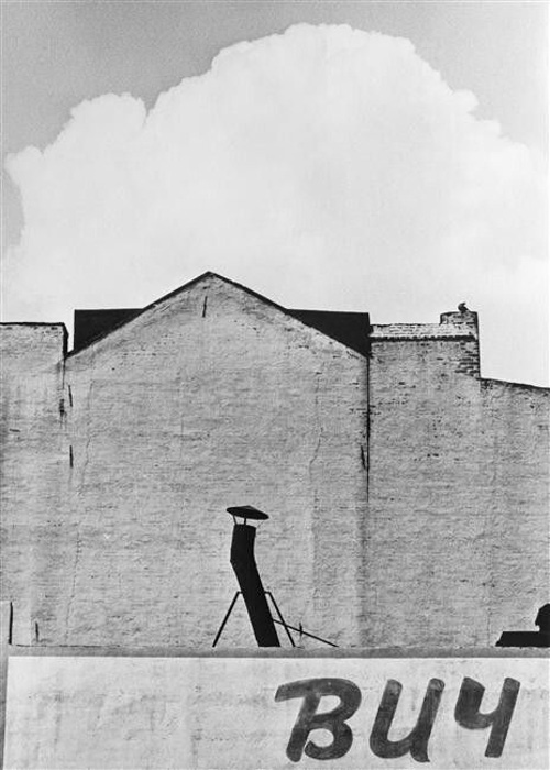 Black and white street photo of a building under cloudy sky by André Kertész - famous street photographers