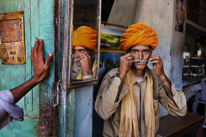 A street photography portrait of a man in orange turban holding his mustache by Steve Curry