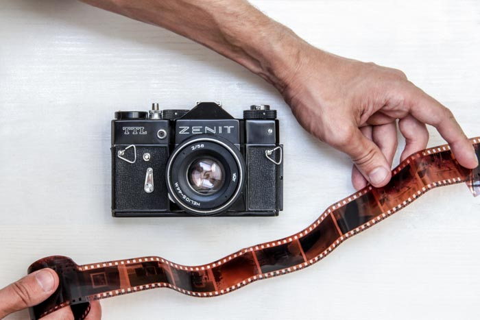 An overhead shot of a Zenit film camera on white background with a person holding a roll of film negative beside it - using film for street photography