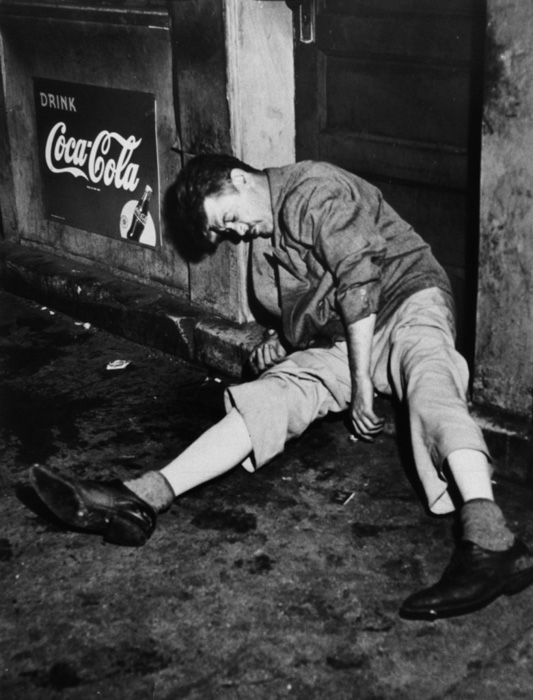 A WeeGee photography of a drunken man passed out in a doorway - types of street photgraphy