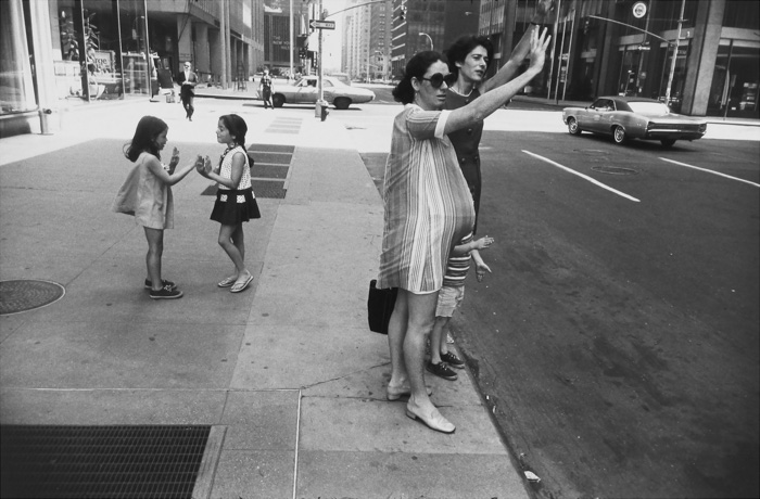 A candid shot of a people hailing a taxi cab on a busy roadside by Gary Winogrand - types of street photography