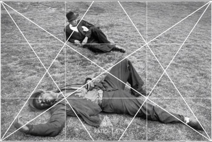 A Henri Cartier-Bresson photo of a two men lying on grass, with composition grid overlayed