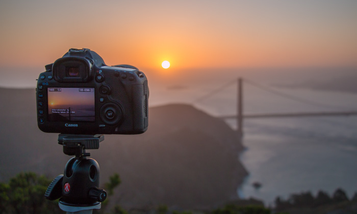 A DSLR camera set up on a Manfrotto tripod to capture a beautiful sunset