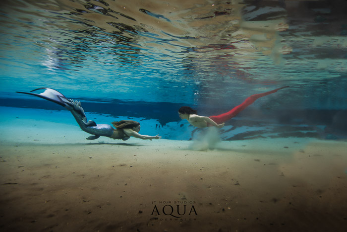 An underwater photography advertising shot of two mermaids