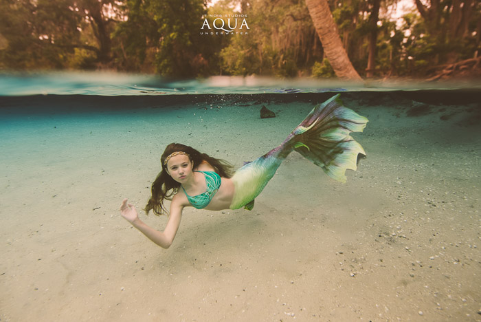 Stunning underwater photography shot of a young mermaid girl swimming underwater