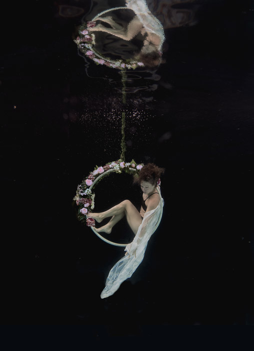 Beautiful and atmospheric photo of a girl posing underwater on a hoop