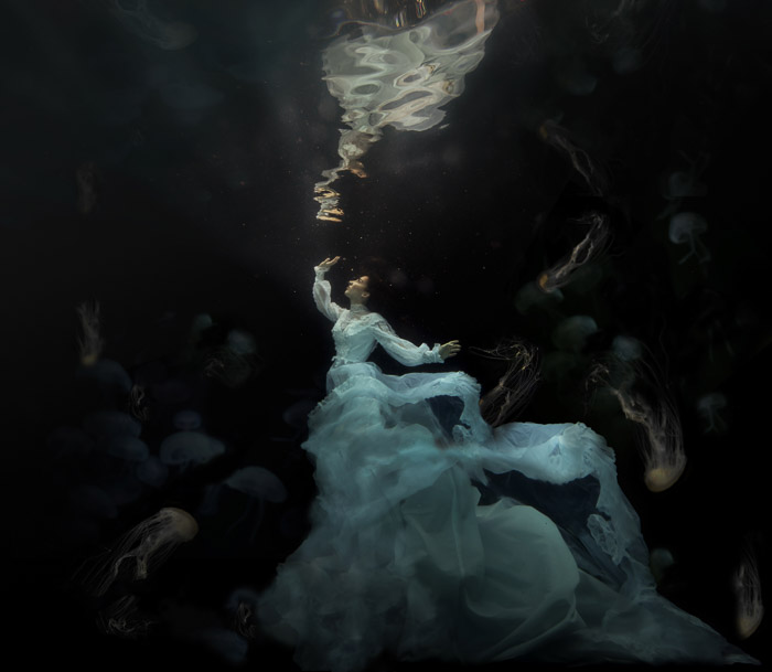 dreamy photo of a woman with flowing white dress underwater