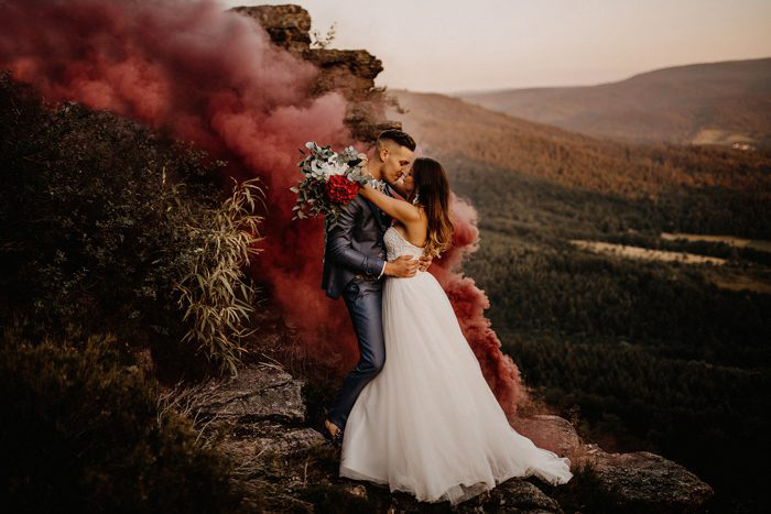 A newlywed couple embracing in an atmospheric landscape with smoke behind them - best wedding blogs to follow