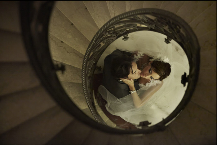 Photo of a bride and groom framed by a spiral starcase