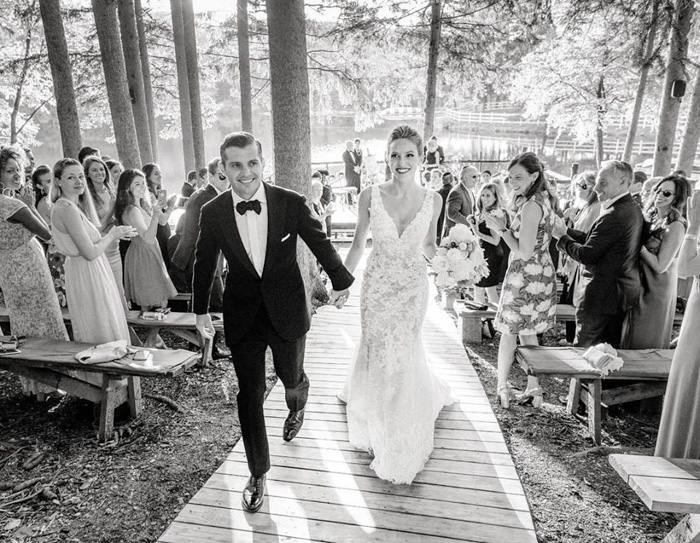 Black and white wedding portrait of the couple walking down the aisle by Heather Waraksa - best wedding blogs