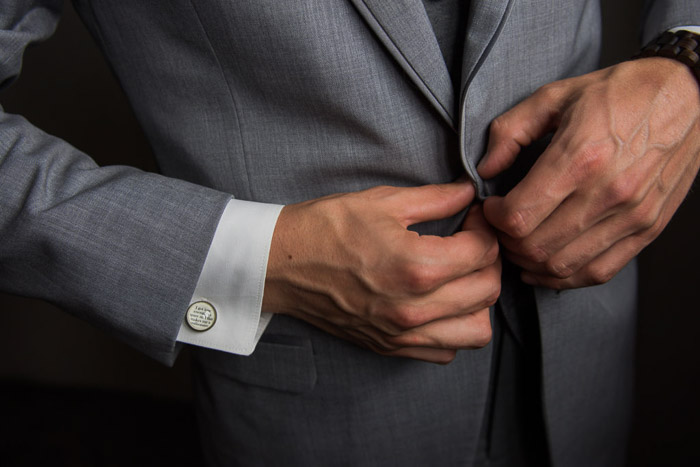 A closeup wedding portrait of the groom buttoning his jacket