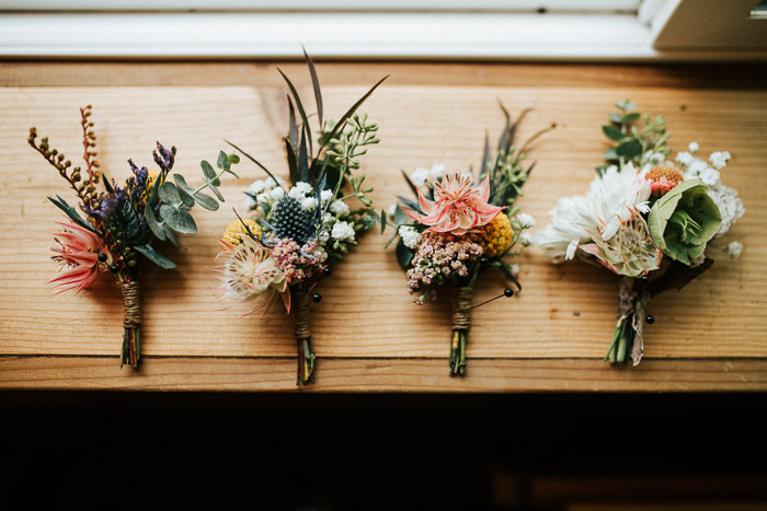 Overhead still life of four wedding flower bouquets on a wooden surface