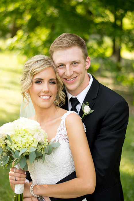 A portrait of the bride and groom embracing outdoors
