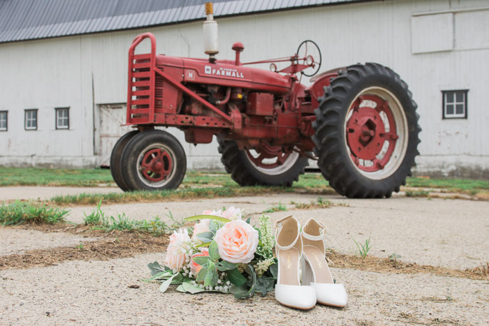 A wedding photography still life of a pair of bridal shoes and bouquet with a red tractor in the background
