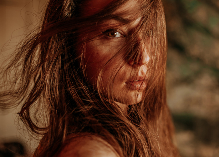Beautiful close up portrait of a girl with hair covering her face, shot using ambient lighting for a dreamy effect