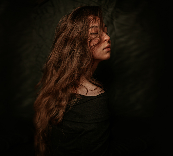Atmospheric portrait of a female model posing against a black background - great selfie poses