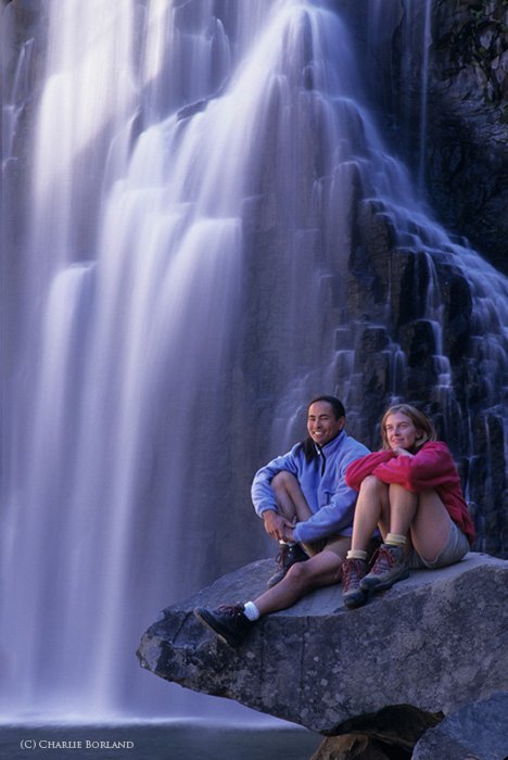 two campers sitting on a rock in front of a waterfall