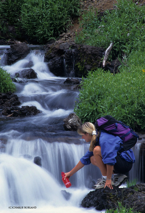 woman refilling her red waterbottle at a rocky river on an adventure photography trip